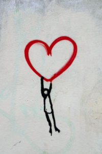 Line drawing of a person flying midair hanging onto the bottom of a heart.